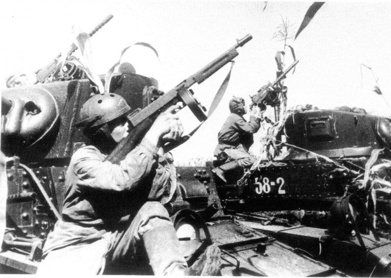 Советские танкисты с танками М3А1 «Стюарт», в американских шлемофонах, с пистолетом-пулеметом Томпсон М1928А1 и пулеметом М1919А4. Американская техника поставлялась по ленд-лизу полностью укомплектованной — с экипировкой и даже стрелковым оружием для экипажа.